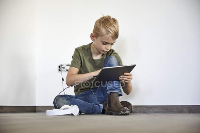 Pequeño niño jugando en la tableta digital mientras está sentado en una casa nueva - foto de stock