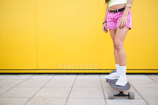 Low section of young woman standing on longboard in front of yellow wall — стокове фото