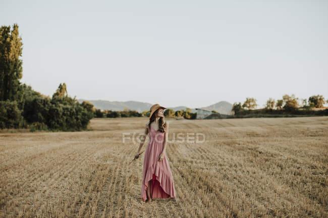 Donna che indossa abito mentre in piedi al campo di grano contro il cielo limpido durante il tramonto — Foto stock