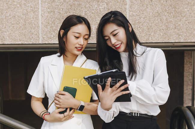 Collèges travaillant ensemble sur tablette numérique — Photo de stock