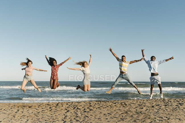 Alegre jóvenes amigos saltando con la mano levantada en la playa durante el día soleado - foto de stock