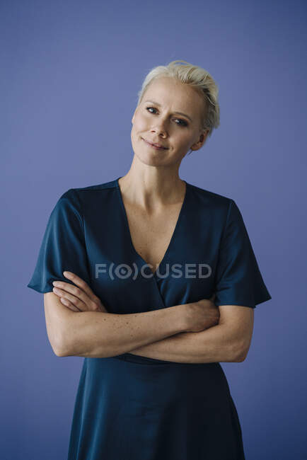 Confident businesswoman with arms crossed standing against blue background — Stock Photo