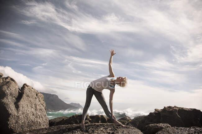 Женщина практикует триконасану на скалах против неба — стоковое фото