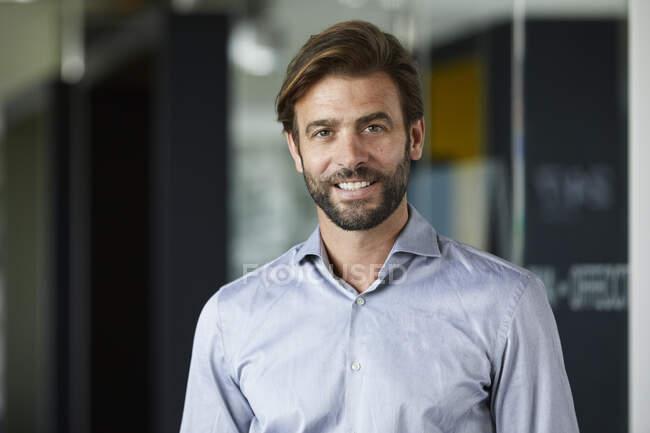 Lächelnder Geschäftsmann steht im Büro gegen Glaswand — Stockfoto