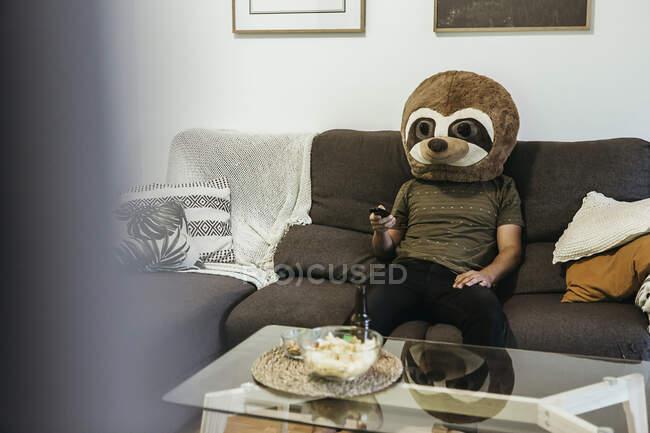 Середній чоловік у плюшевому ведмедику дивиться телевізор у вітальні. — стокове фото