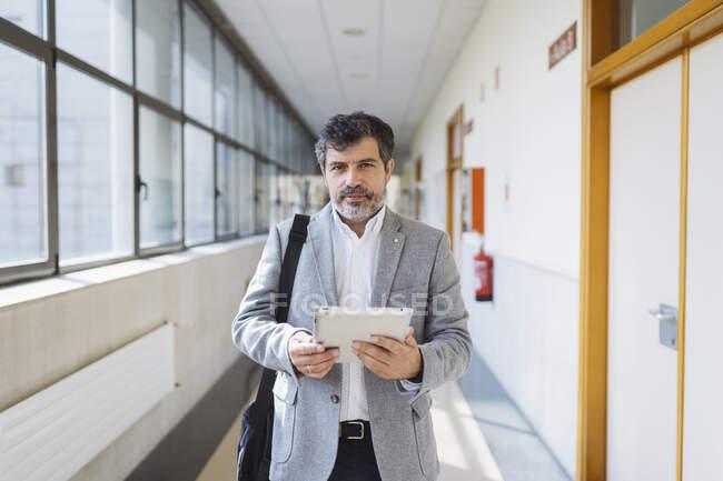 Зрілий професор чоловічої статі тримає цифрову табличку в коридорі в університеті. — стокове фото