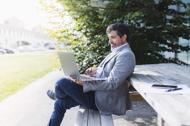 Бізнесмен за допомогою ноутбука спирається на стіл. — стокове фото