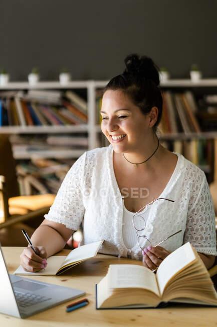 Sorrindo jovem escrevendo no livro enquanto estudava sobre laptop na mesa no café — Fotografia de Stock
