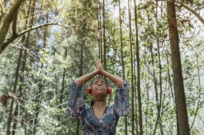 Молодая женщина с закрытыми глазами слушает музыку через наушники во время медитации против деревьев в парке — стоковое фото