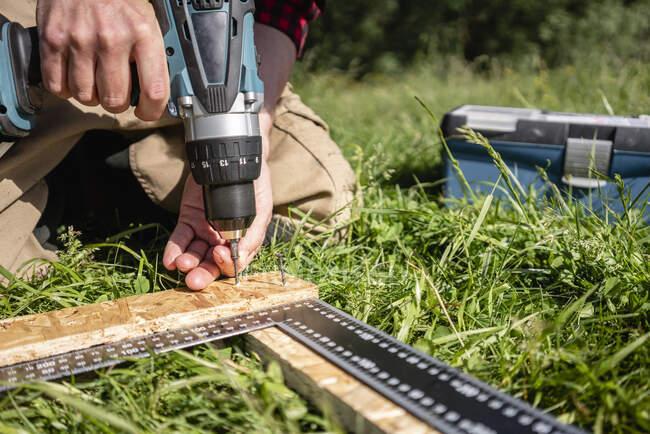 Tischler bohrt bei sonnigem Tag Schrauben auf Planke — Stockfoto