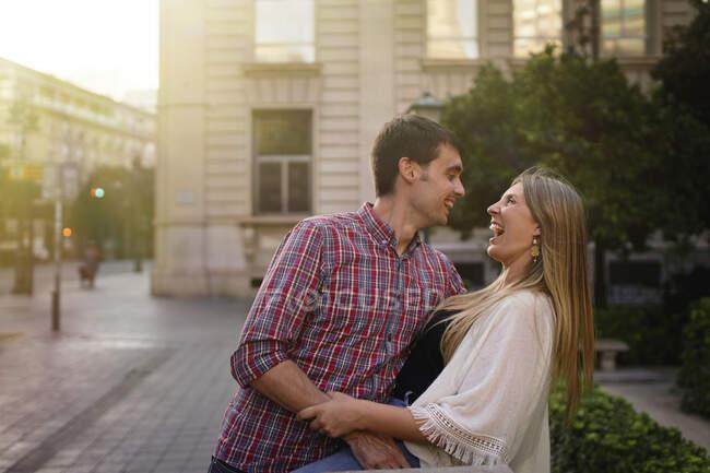 Pareja feliz de pie en la calle en la ciudad - foto de stock