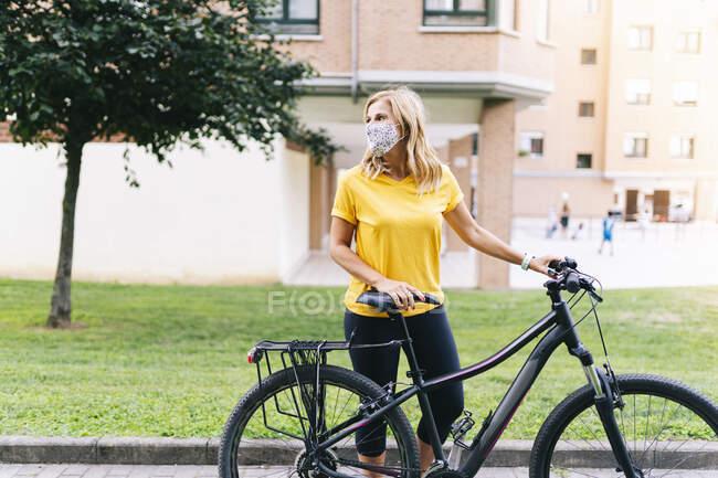 Доросла жінка з захисною маскою, що дивиться убік, стоячи з велосипедом на стежці в місті. — стокове фото