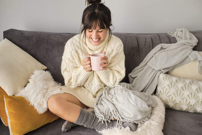 Happy woman having coffee in mug while sitting on sofa at home during winter — Fotografia de Stock