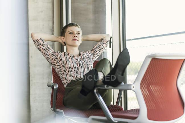 Relaxado empresária sentado na cadeira no escritório ter uma pausa — Fotografia de Stock