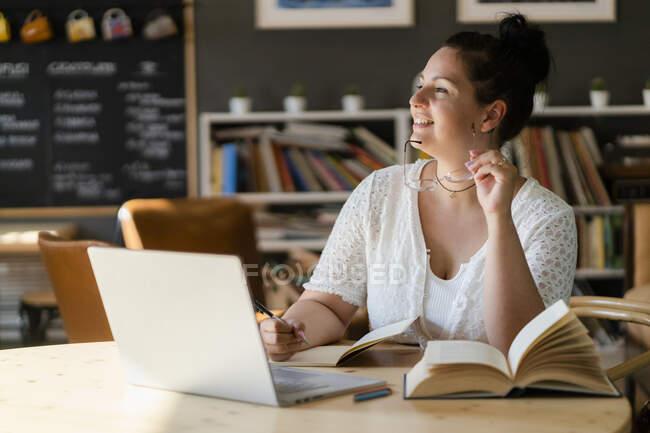Mulher voluptuosa com livros e laptop na mesa contemplando enquanto está sentado no café — Fotografia de Stock