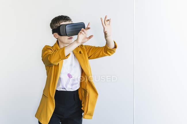 Бізнесниця дивиться через симулятор віртуальної реальності, стоячи проти стіни в офісі — стокове фото