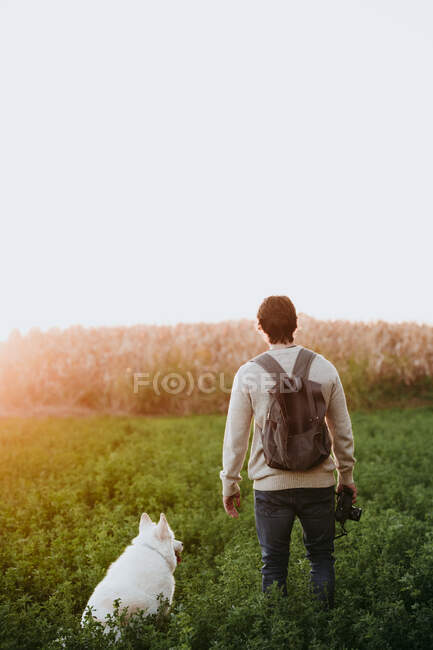 Man with backpack holding camera while sanding by dog at field — Stock Photo