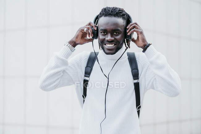 Hombre feliz usando auriculares mientras está de pie contra la pared blanca - foto de stock