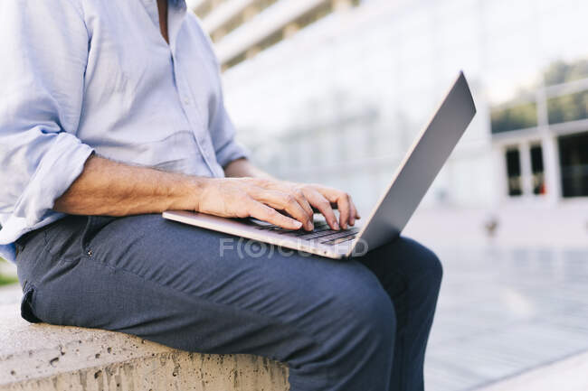 Businessman using laptop while sitting at office park — Stock Photo