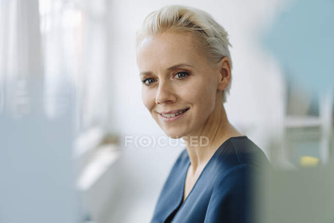 Close-up of smiling female entrepreneur seen through window in office — Stock Photo