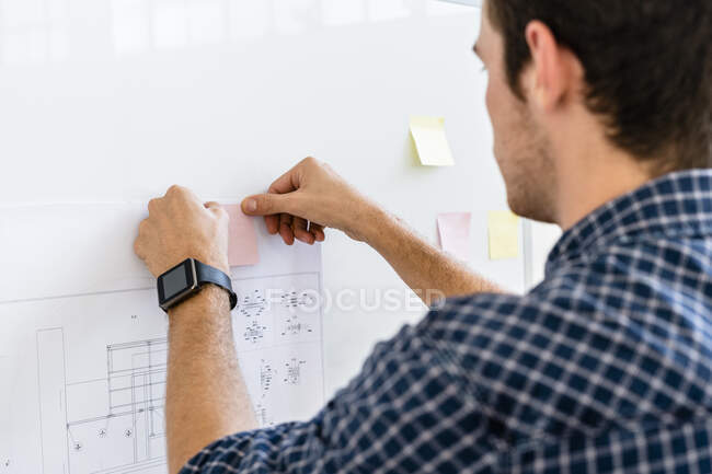 Man putting adhesive note on whiteboard while standing at office — Stock Photo