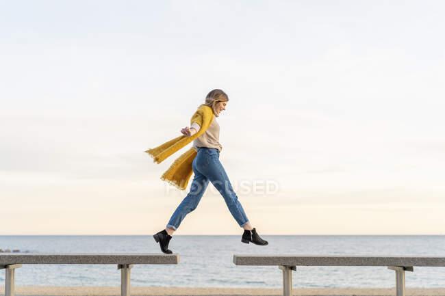 Giovane donna allegra che salta da una panchina all'altra sul lungomare contro il cielo durante il tramonto — Foto stock