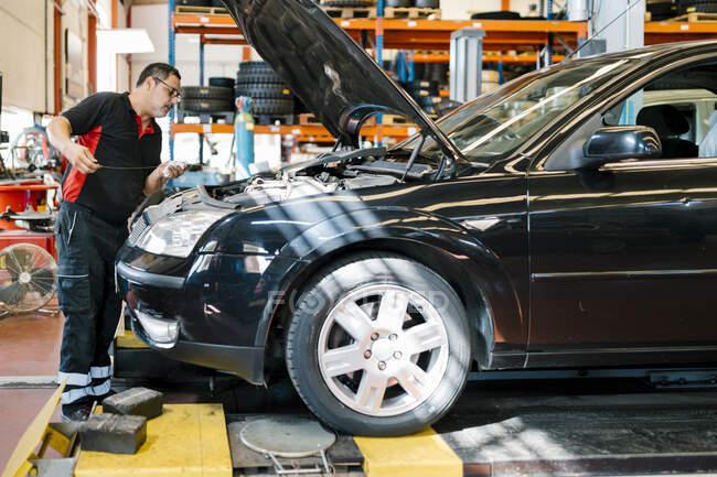 Чоловік - механік ремонтує автомобіль, стоячи в автомайстерні. — стокове фото