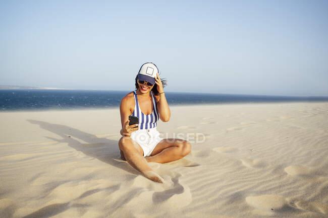 Donna sorridente scattare selfie mentre seduto sulla sabbia in spiaggia contro il cielo blu chiaro durante la giornata di sole — Foto stock