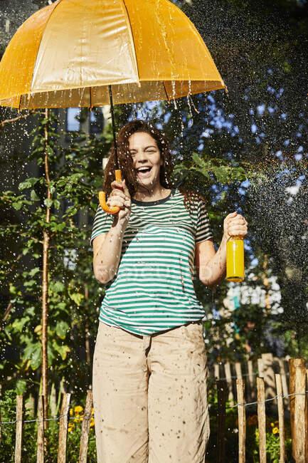 Joven mujer riendo con paraguas y limonada en el jardín — Stock Photo
