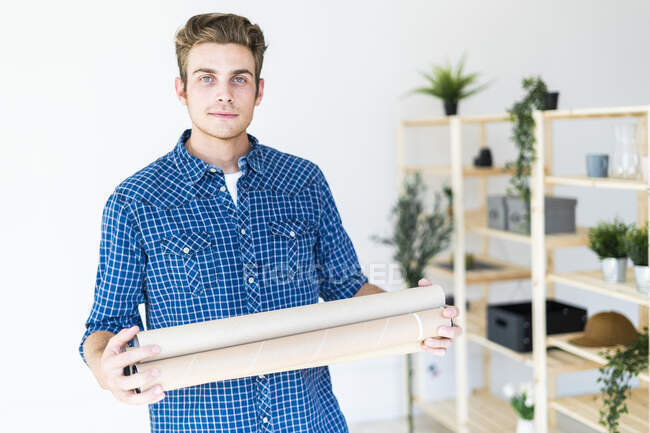 Young man holding blueprint tube while standing at office — Stock Photo
