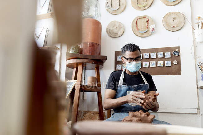 Potter wearing mask holding clay while sitting in workshop — Stock Photo