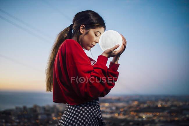 Mujer joven con los ojos cerrados sosteniendo la lámpara en forma de luna contra el cielo al atardecer - foto de stock