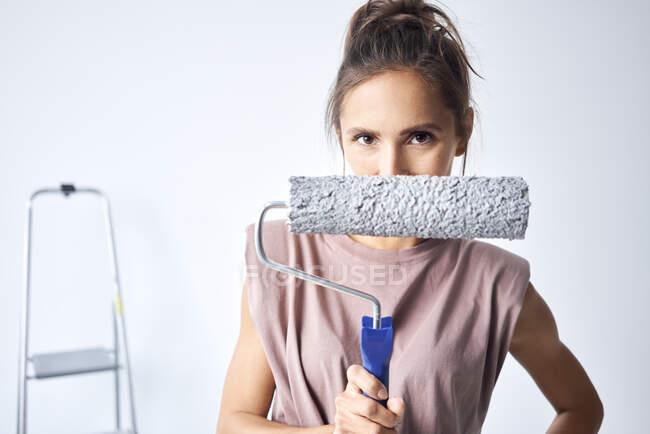 Молода жінка, що тримає фарбу на ролику, стоячи вдома. — стокове фото