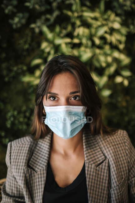 Mujer joven con mascarilla protectora sentada en el café - foto de stock