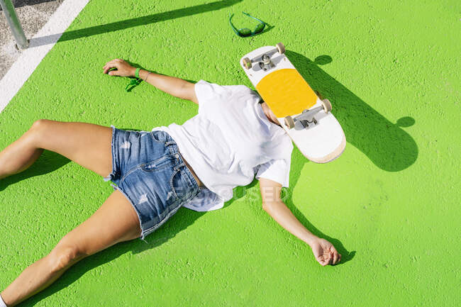 Mature woman with skateboard on face lying over green footpath — Stock Photo