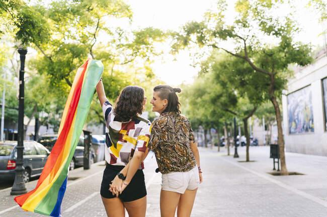 Лесбійська пара тримає прапор веселки, стоячи на стежці в місті. — стокове фото