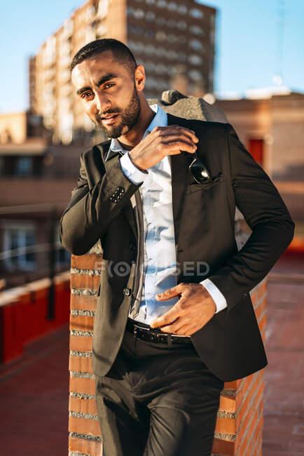 Jeune homme entrepreneur mettre des lunettes de soleil dans la poche tout en se tenant sur le toit — Photo de stock