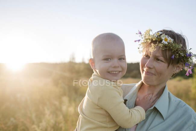 Счастливая женщина носит венок во время ношения сына в солнечный день — стоковое фото