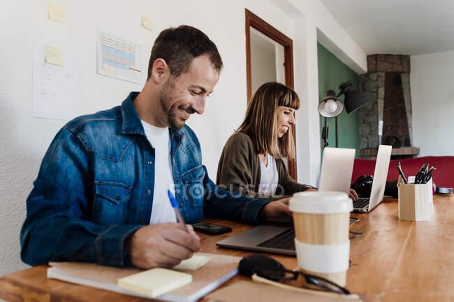 Усмішка бізнес-пари працює на ноутбуці в домашньому офісі. — стокове фото