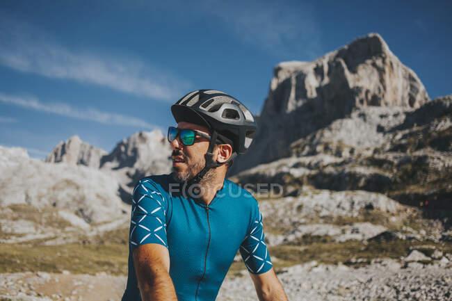 Мужской велогонщик смотрит в сторону знаменитого национального парка Пикос-де-Европа в солнечный день, Кантабрия, Испания — стоковое фото