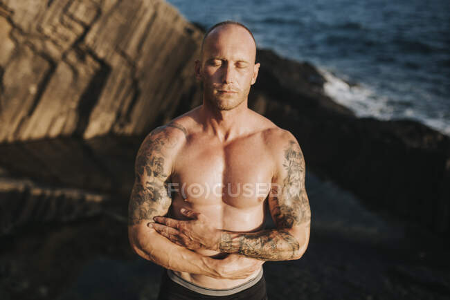 Tattooed nudist standing on volcanic rocks by the sea with arms crossed — Stock Photo