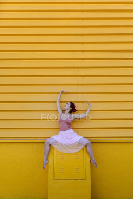 Young woman with arms raised dancing on seat against yellow wall — стокове фото