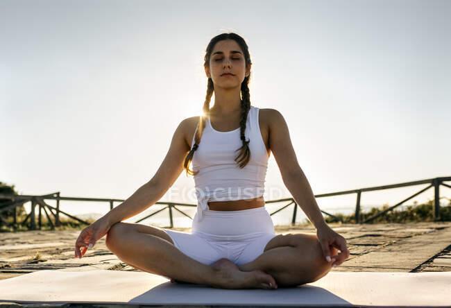 Молодая женщина с закрытыми глазами медитирует на коврике против ясного неба на закате — стоковое фото