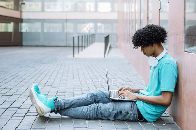 Young man using laptop while sitting on footpath in city - foto de stock
