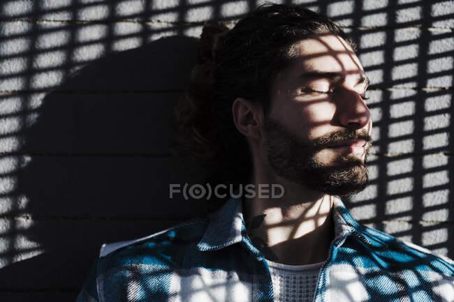 Uomo con gli occhi chiusi e l'ombra sul viso appoggiato al muro — Foto stock