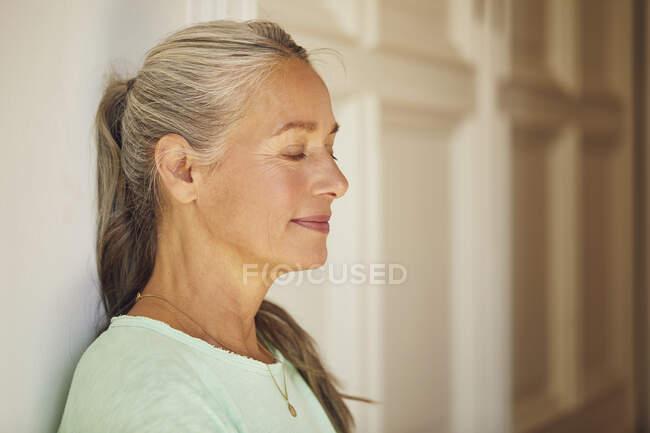 Mujer arrugada con los ojos cerrados por la puerta en casa - foto de stock