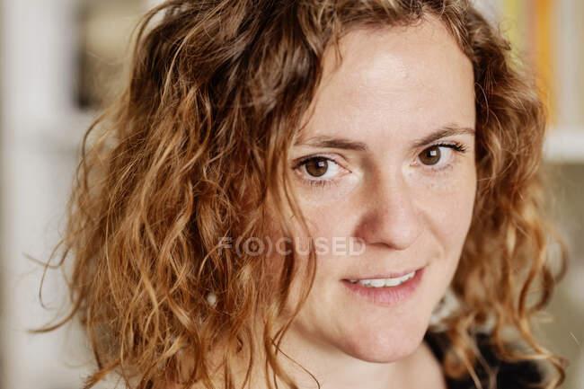 Збільшений портрет дорослої жінки з хвилястим волоссям вдома. — стокове фото