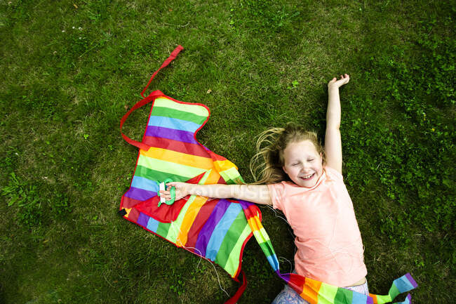Cheerful girl holding kite while lying on grass in park — Stock Photo