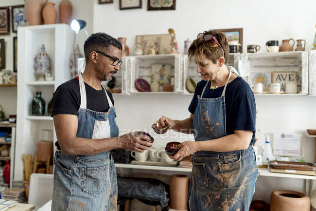 Coworkers holding potteries while standing in workshop — Stock Photo