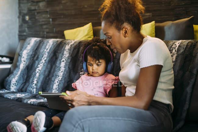 Мама показувала дочці цифрову табличку з навушниками, сидячи вдома на дивані. — стокове фото
